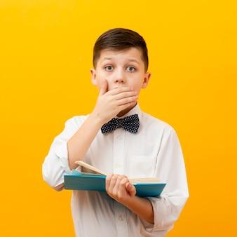 驚いた本を持った少年