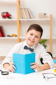 Улыбающийся маленький мальчик читает