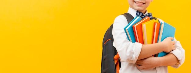 書籍のスタックを運ぶクローズアップ少年