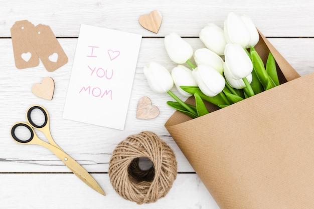 Вид сверху белых тюльпанов на деревянный стол