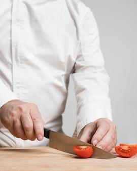Крупным планом шеф-повар резки помидоры на деревянной доске