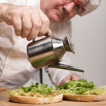 Крупным планом шеф-повар, добавление масла на гуакамоле
