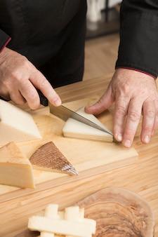 Высокий угол шеф-повар резки сыр на деревянной доске
