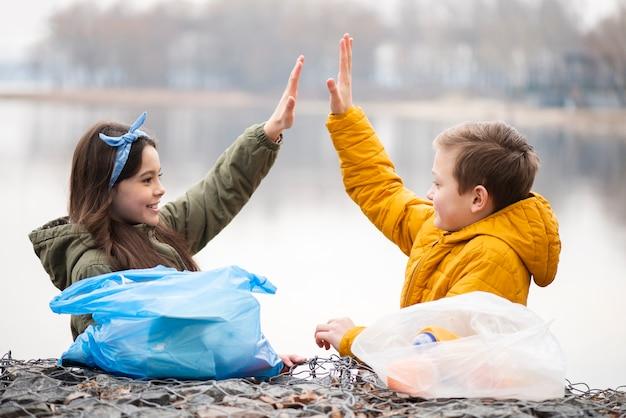 Вид спереди детей, дающих высокие пять