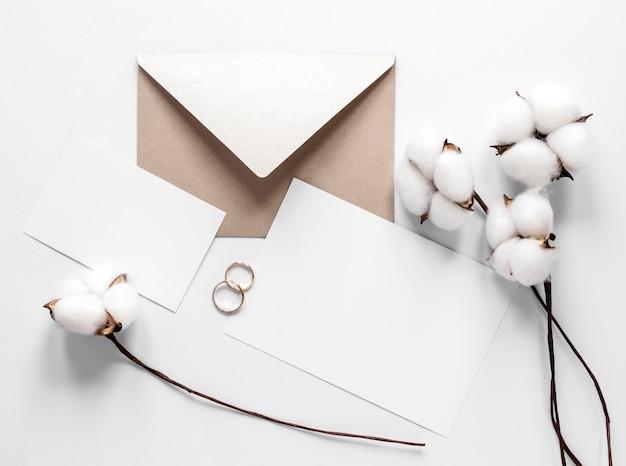 綿の枝の横にある結婚式の招待状