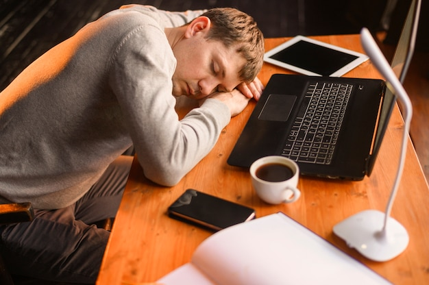 若い起業家が仕事をしすぎて眠りに落ちる