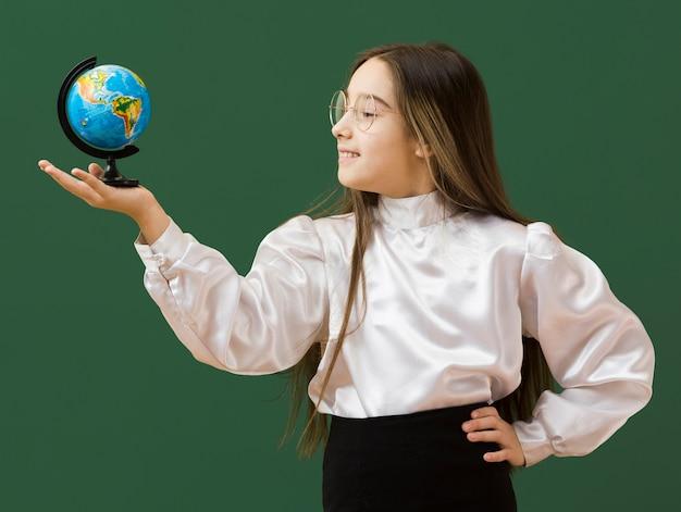 Счастливая девушка, глядя на глобус