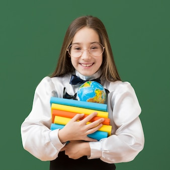 Девушка держит кучу книг
