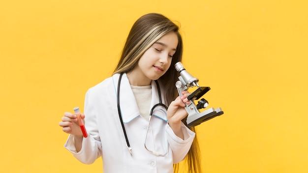 Милая девушка смотря микроскоп