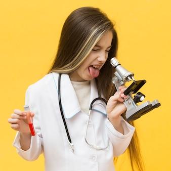 Недовольная девушка смотрит в микроскоп