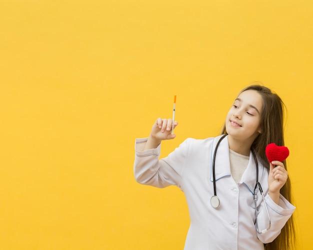 Молодая девушка держит шприц и сердце