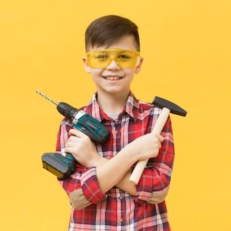 Мальчик держит сверлильный станок и молоток