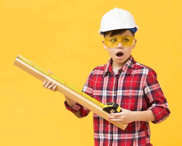 Удивленный мальчик с помощью измерительной ленты