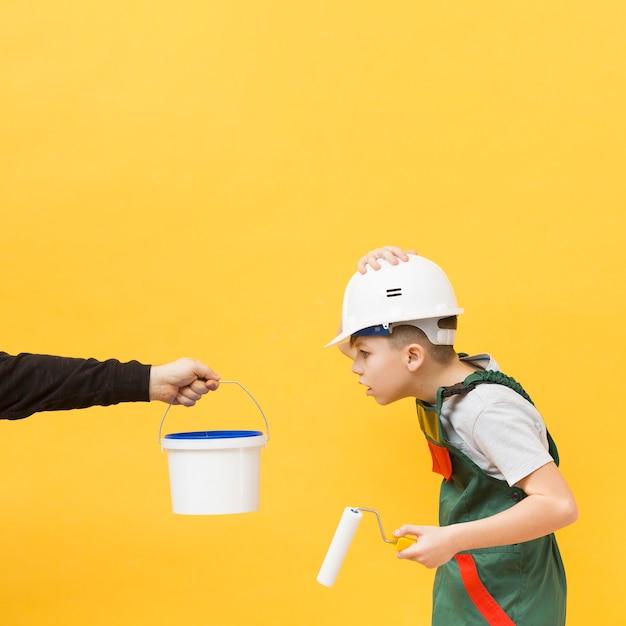 Удивленный мальчик держит малярный валик
