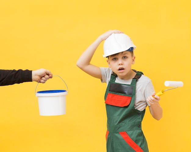 Удивленный ремонтник мальчик с малярным валиком