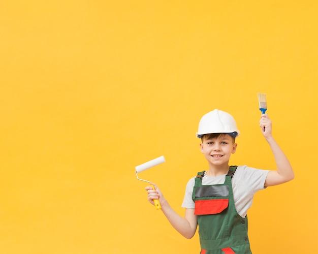 Счастливый мальчик держит инструменты рисования