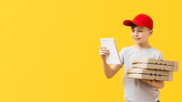 Мальчик доставки пиццы держит блокнот