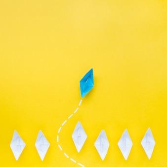 Синий бумажный кораблик перед белыми бумажными корабликами