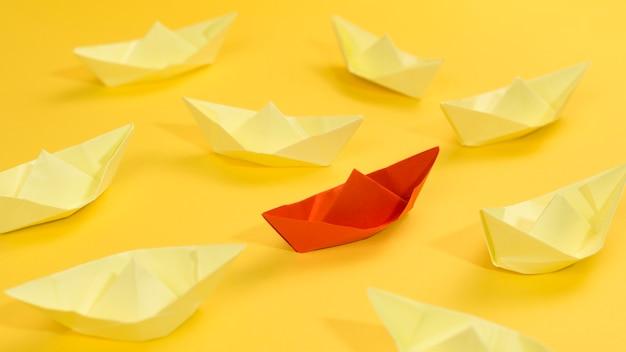 黄色の背景にペーパーボートで抽象的な配置