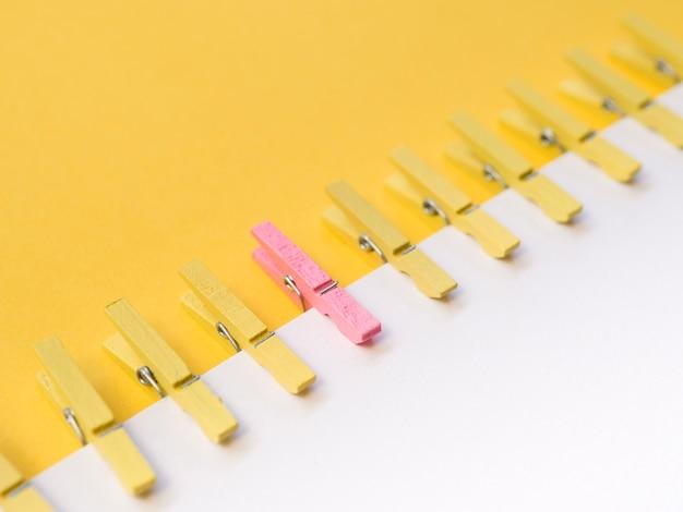 Розовая прищепка в центре желтых прищепок