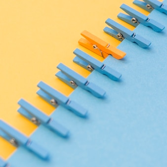 青いものに囲まれたオレンジ色の洗濯はさみ