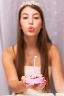 Девочка-подросток дует на день рождения свечи
