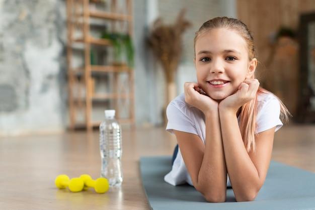 Милая девушка позирует на коврик для йоги