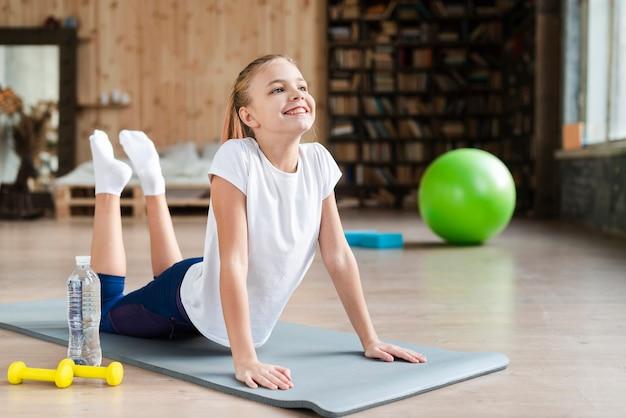 Милая девушка практикующих йогу на коврике