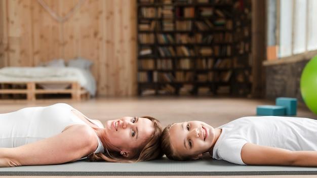 Мать и дочь лежат на коврик для йоги