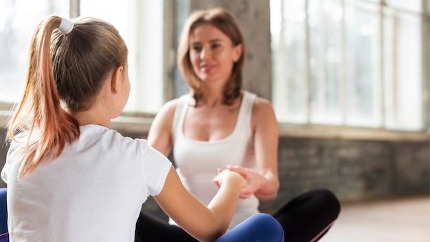 Мать и дочь крупного плана держа руки на циновках йоги