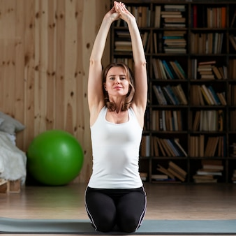 Женщина растягивается на коврик для йоги