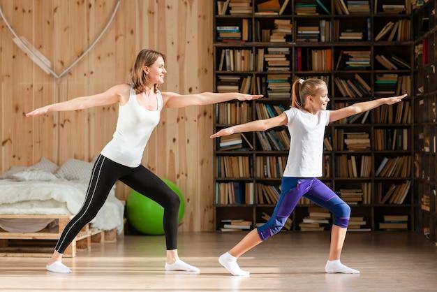 Мать и дочь делают позу йоги
