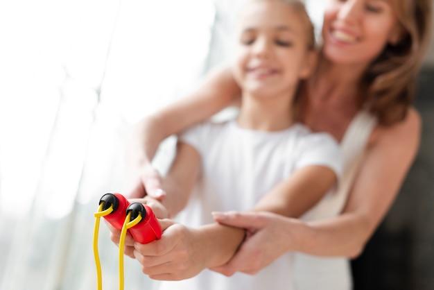 Мать крупным планом учит дочь, как использовать скакалку