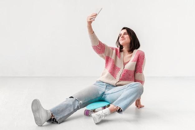 Девушка с скейтбордом принимая селфи