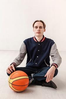 バスケットボールの横に座っている少年