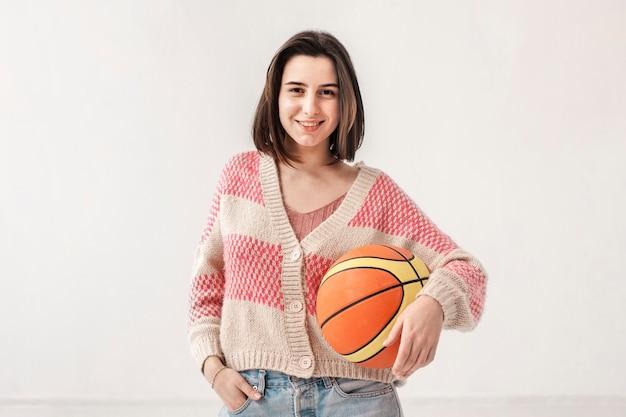Улыбающаяся девушка держит баскетбольный мяч