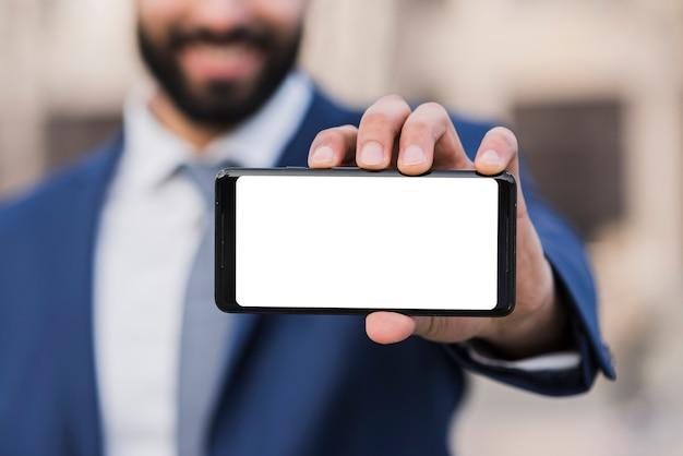 Крупным планом деловой человек, держащий мобильный