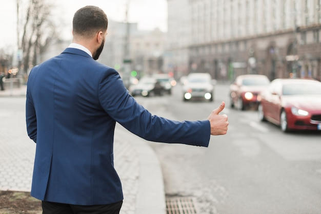 タクシーをこするビジネスマン