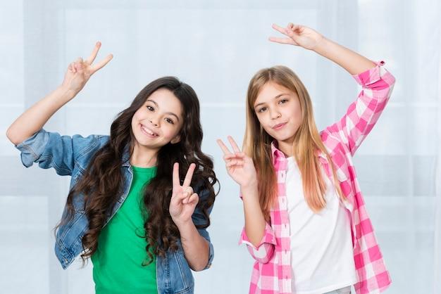 ピースサインを示す若い女の子