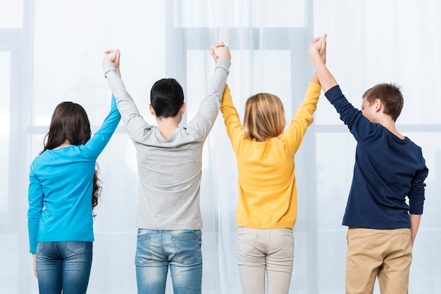 Низкий угол дети с поднятыми руками