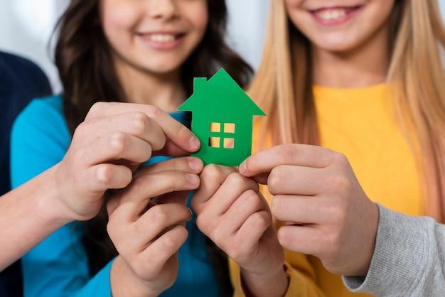 Крупным планом дети держат игрушечный домик