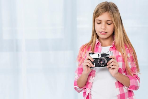 Молодая девушка держит камеру