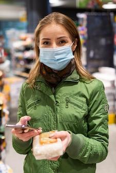 Девушка на улице покупает товары для карантина