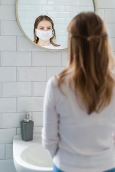 鏡で見ている検疫の女性
