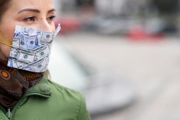 自家製のお金の顔のマスクを着ている女性