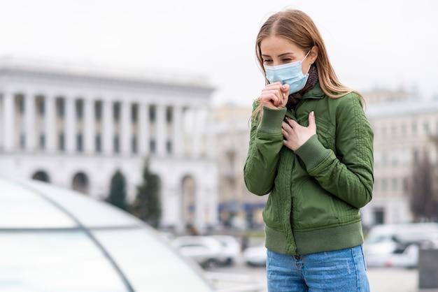 公共スペースで手術用フェイスマスクを着ている女性