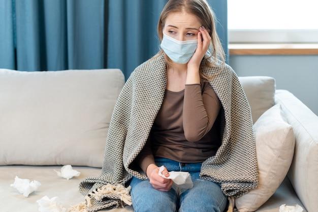 検疫に滞在し、熱を持っているマスクを持つ女性