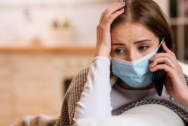 電話で話している検疫にとどまるマスクを持つ女性