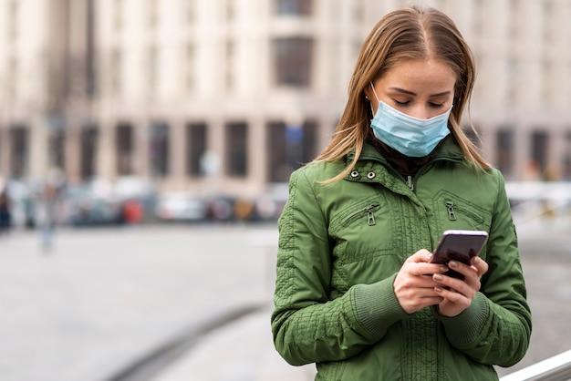 Женщина на улице носить маску и с помощью мобильного телефона