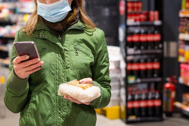 お店で彼女の携帯電話を使用して防護マスクを持つ女性